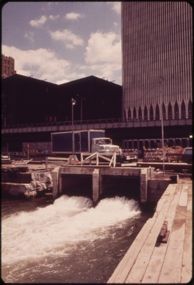 'Outflow of Drainage from the World Trade Center, New York's Latest Giant, Under Construction between Vesey and Liberty Streets in Lower Manhattan. There Is No Provision for Waste Treatment as Is the Case with All Westside Buildings, Sewage Will Go Directly Into the Already Badly Polluted Hudson River - Wil Blanche.'
